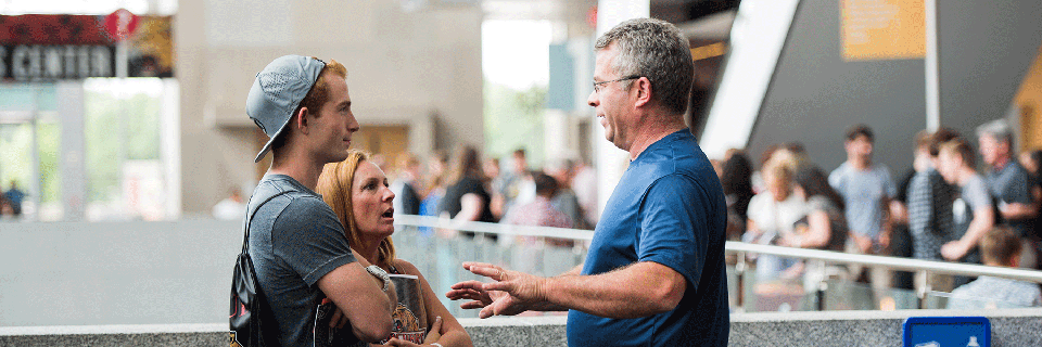 A photo of a mother and son asking a question to a staff member on campus.